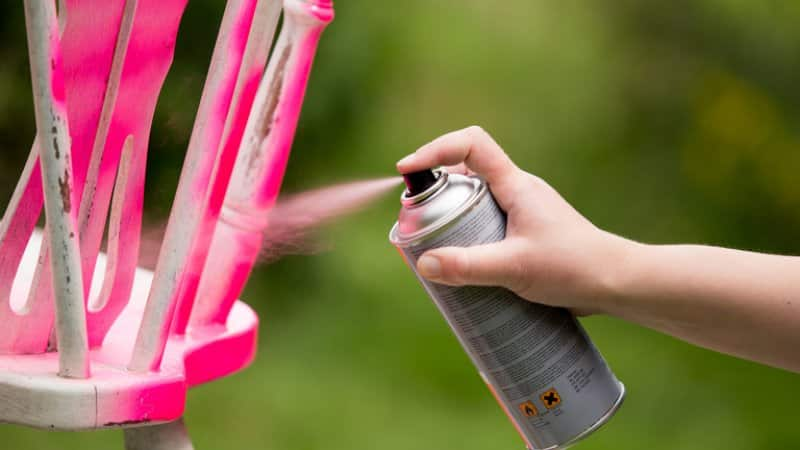 Spray painting an old chair pink (Photo by Levas / Shutterstock.com)