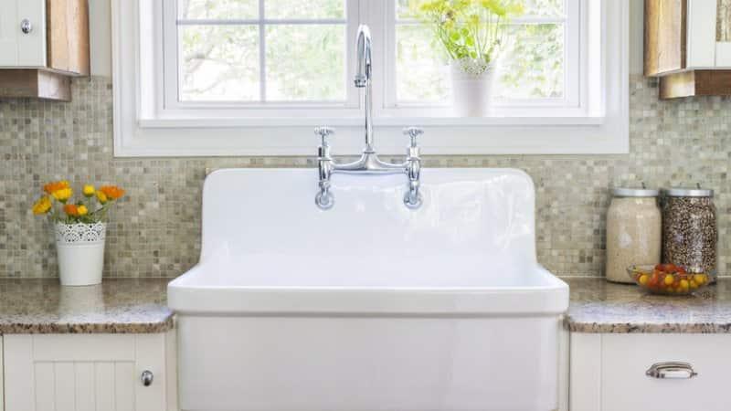 Large white kitchen sink and grey porcelain backsplash (Photo by Elena Elisseeva/Shutterstock.com)