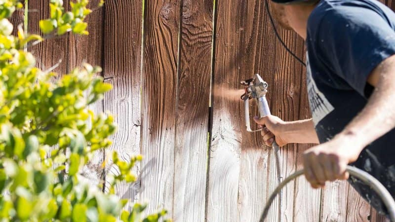 Professional painter spraying fence with wood stain. (Photo by Andy Dean - stock.adobe.com)