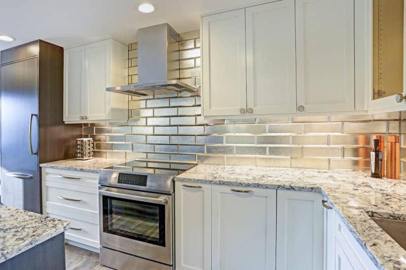 Kitchen with stainless subway tile backsplash and white cabinets (Photo by Javani LLC - stock.adobe.com)