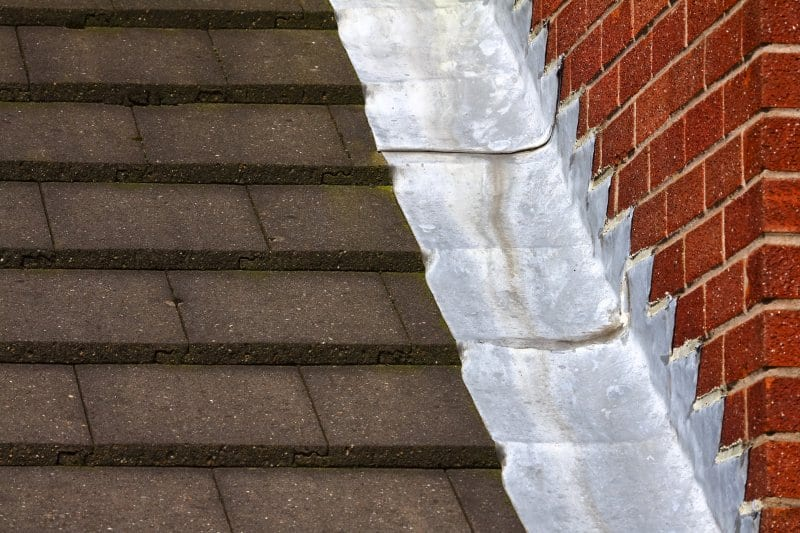 A roof with step flashing going up a brick wall (Photo by Andrew Gardener - adobe.stock.com)