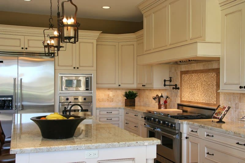 Luxury kitchen with stone and tile backsplash, white cabinets and kitchen island (Photo by Mark Breck - stock.adobe.com)