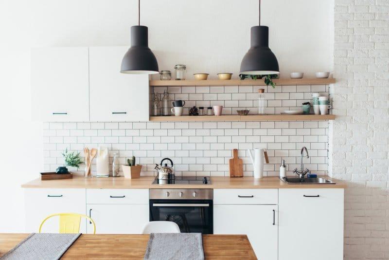 Modern kitchen with white subway tile backsplash, white cabinets, wood open shelves and black pendant lights (Photo by undrey - stock.adobe.com)