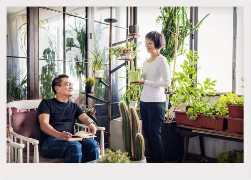 man and woman talking in sunroom with lots of plants (Photo by © Yongyuan/Getty Images)
