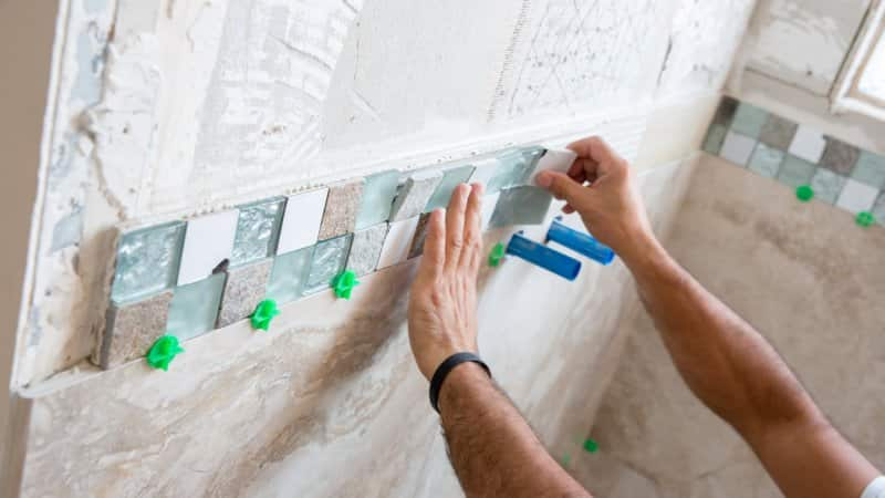A professional installing a tiled border for the shower wall (Photo by JodiJacobson/iStock / Getty Images Plus via Getty Images)