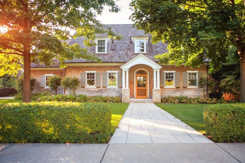 a two story traditional house with brick siding, stone walkway and hedge bushes (Photo by soupstock - stock.adobe.com)