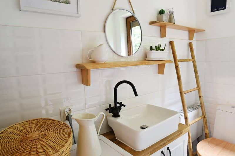 Bathroom with wooden ladder next to toilet, open wood shelves, small square sink, and white tile (Photo by photosbysabkapl – stock.adobe.com)