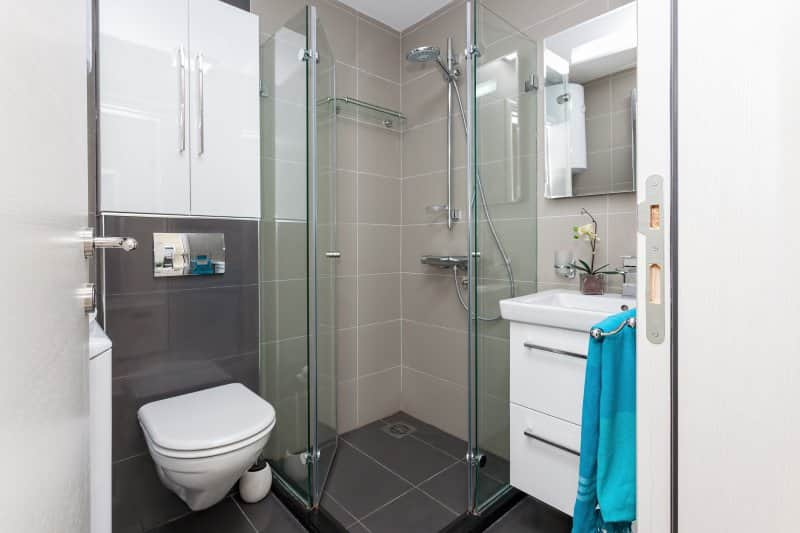 Small modern bathroom with gray tiles, glass shower, wall-hung toilet, and white vanity and cabinets (Photo by miriristic – stock.adobe.com)