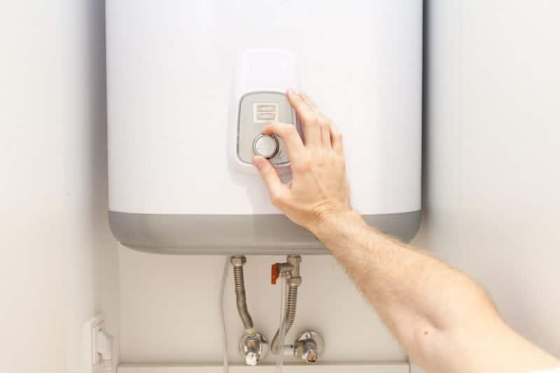 a hand turning the thermostat of a water heater (Photo by ©  brizmaker/ iStock / Getty Images Plus/Getty Images.)