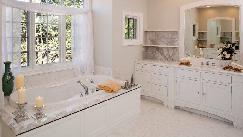 A white toned bathroom with a bathtub (Photo by jimkruger/E+ via Getty Images)