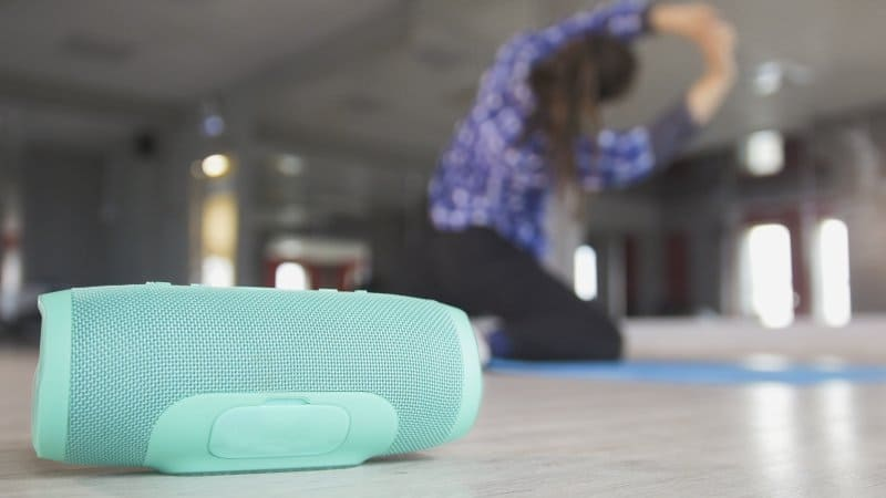 A woman stretching on the floor of her home gym with a turquoise wireless speaker (Photo by Barselona Dreams - stock.adobe.com)