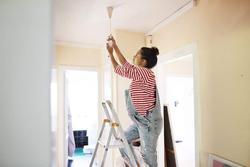 woman in overalls stands on a ladder and change hanging lightbulb from ceiling (Photo by  Klaus Vedfelt/DigitalVision via Getty Images)
