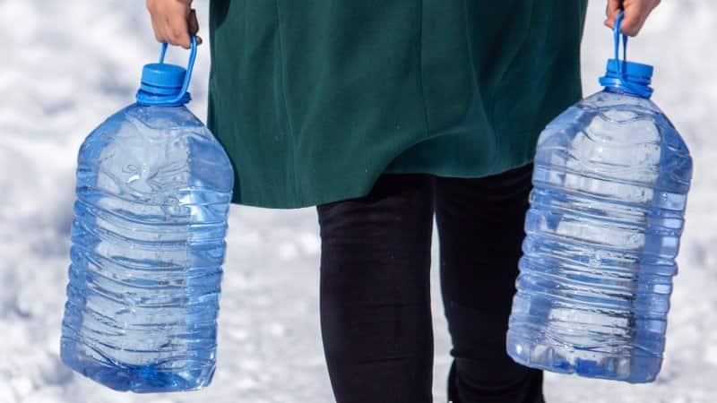 A woman carrying water in plastic bottles (Photo by schankz - stock.adobe.com)