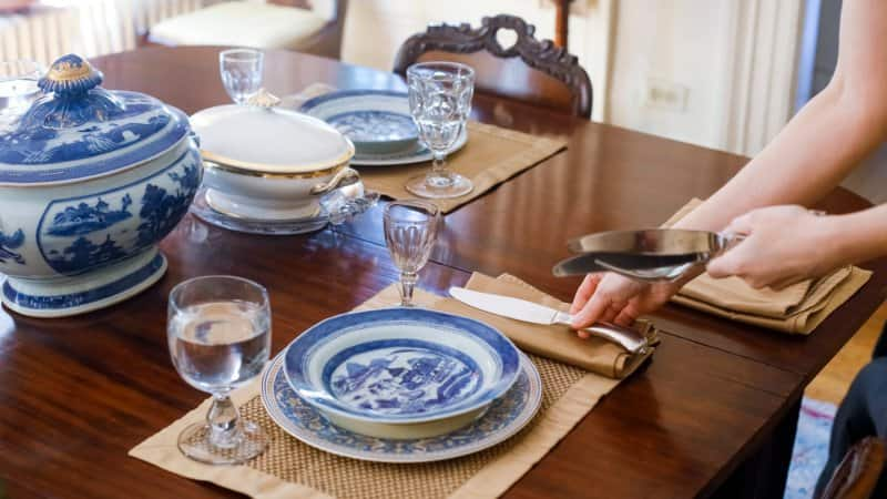 A woman's hand setting the table with antique tableware (Photo by Julien Mcroberts via Getty Images)