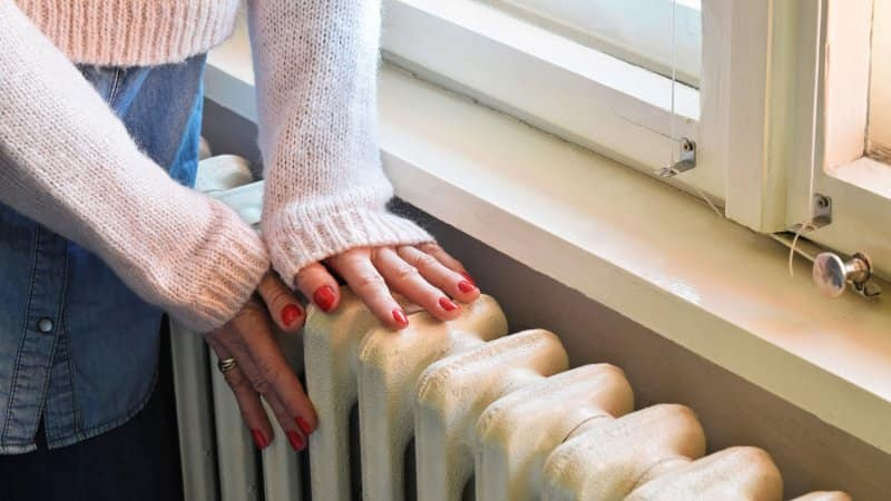 A woman's hands warming on a radiator (Photo by zvonko1959/iStock/Getty Images Plus via Getty Images)