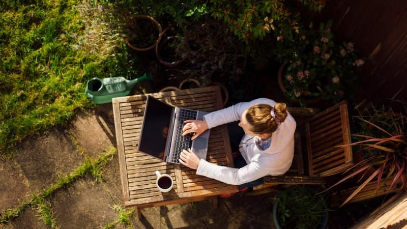 A woman working with her laptop in a garden (Photo by Gary Yeowell/DigitalVision via Getty Images)