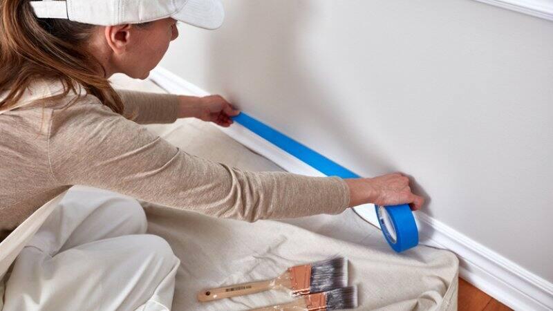 Woman taping wall to paint trim (Photo by kurhan / Shutterstock.com)