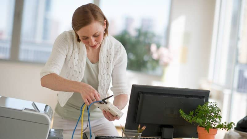 A woman plugging ethernet cable to the router (Photo by Tetra Images via Getty Images)
