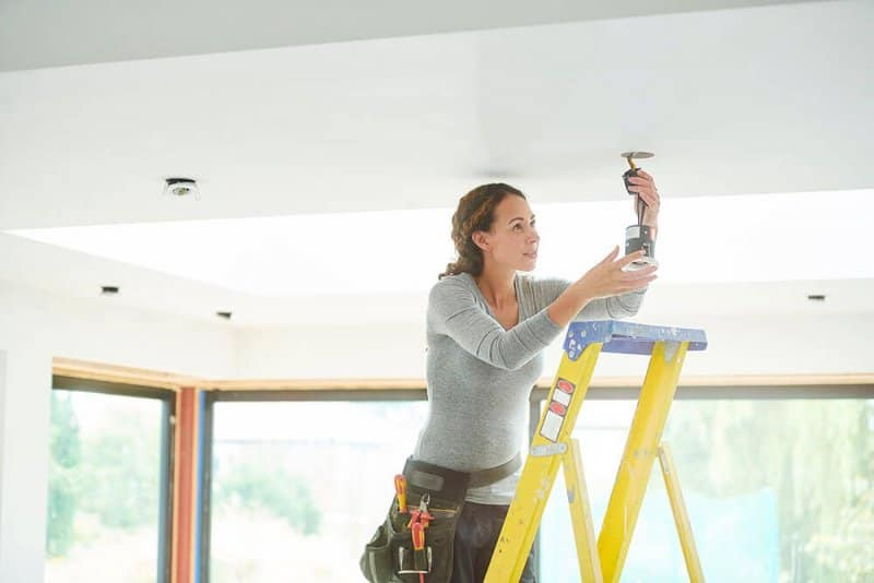 Woman wiring ceiling light (Photo by  sturti/E+ via Getty Images)