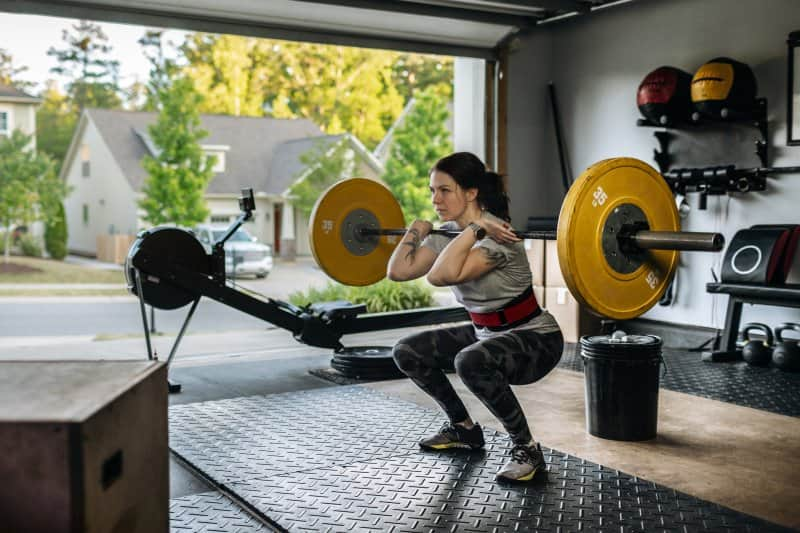 Young woman in gym clothes weight lifting in her garage home gym surrounded by gym equipment (Photo by IngredientsPhoto /  E+ via Getty Images)