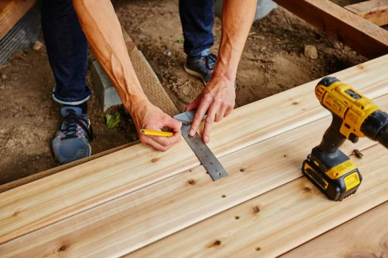 a man drilling wood for a new deck (Photo by © maxwellmonty - stock.adobe.com)
