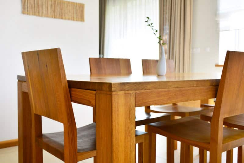 closeup view of medium wood dining table and chairs (Photo by CharMoment - stock.adobe.com)