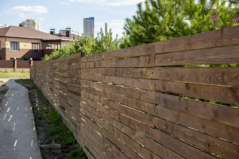a wooden privacy fence running along grass and sidewalk on a suburban street (Photo by Татьяна Антоненко - stock.adobe.com)