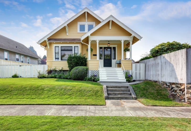 exterior of small house with yellow painted siding, green grass, and concrete sidewalk (Photo by Iriana Shiyan - stock.adobe.com)