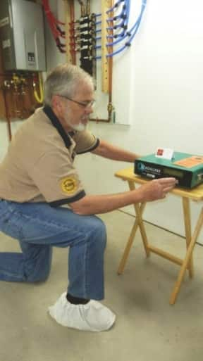 A man on bended knee sets up a radon detector that will monitor the amount of radon in a home