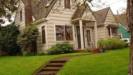 beige gable roof line house with portico porch with assending steps on a lawn.