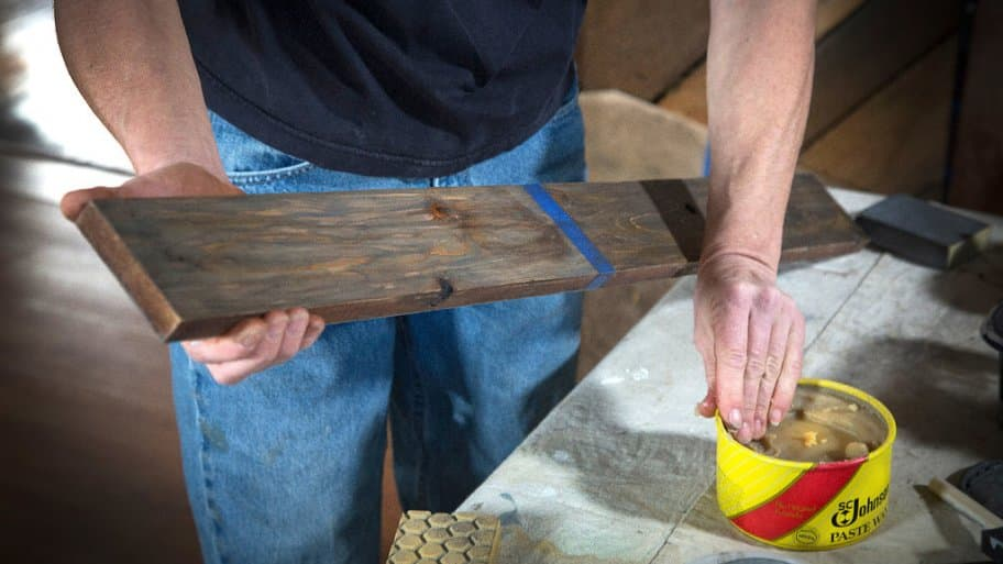 Liza Oates of Wild Zen, Inc. applies paste wax to a board altered with vinegar