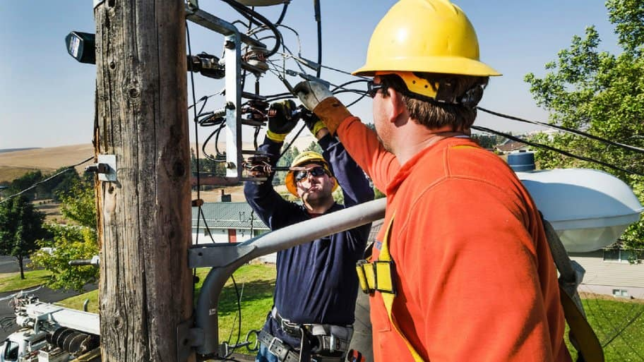 Power line workers working on utility pole