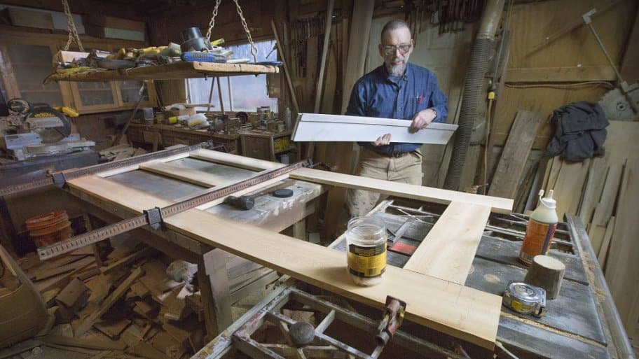 Kerry Barnard, The Front Gate's restoration carpenter, examines the panels of a wooden antique door.