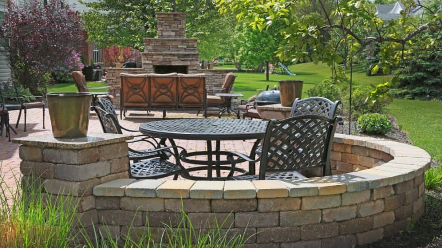 Back yard with stone patio, chairs and fireplace