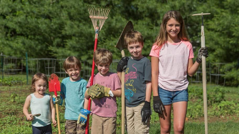 Five children, from youngest to oldest going left to right, all with garden tools