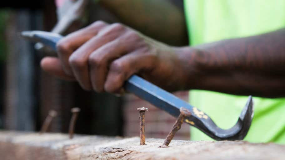 Worker at Southern Pine Co. in Savannah, Georgia removes nails from reclaimed wood