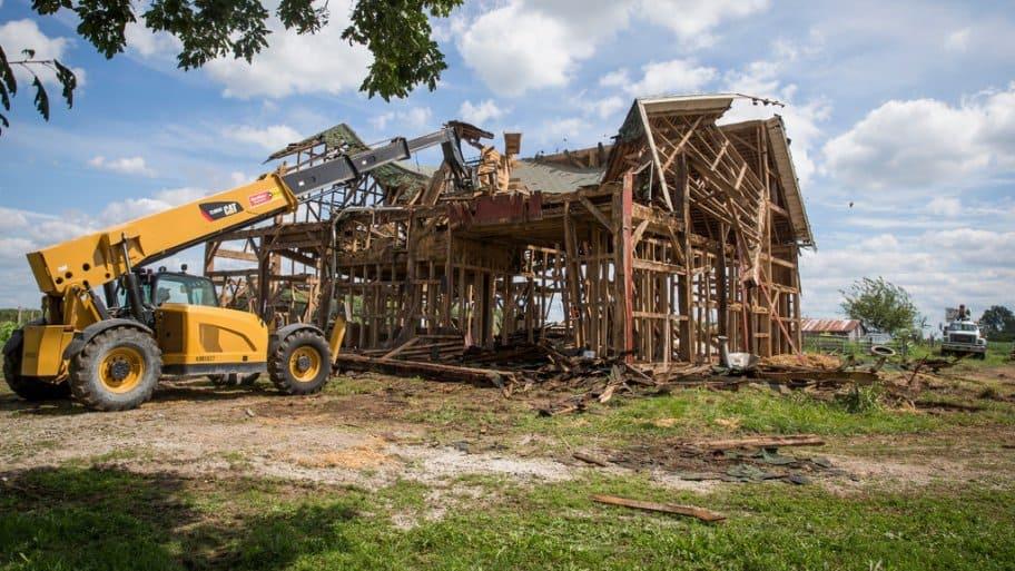 A bulldozer demolishes an old barn in Kokomo, Indiana