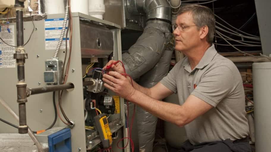 HVAC maintenance technician working on a unit