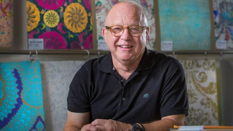 Artist Walter Knabe at his Indianapolis studio with custom wallpaper designs behind him