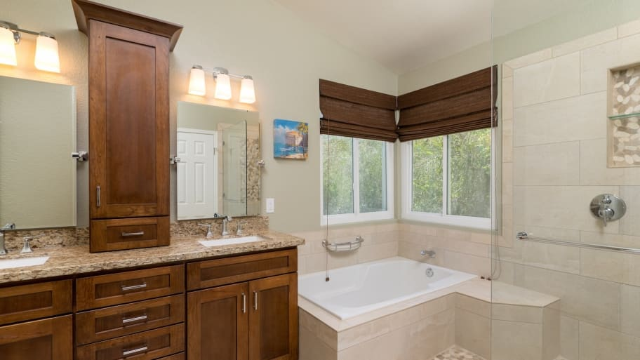 remodeled bathroom with cabinets, tile and tub
