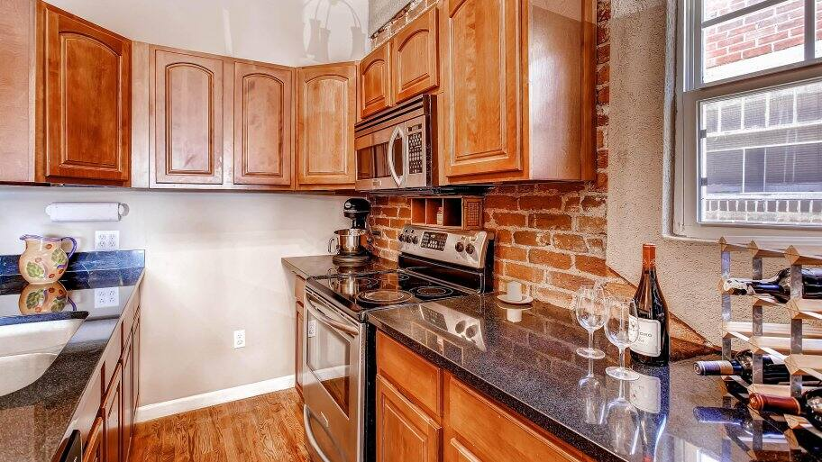 galley kitchen with black granite countertops