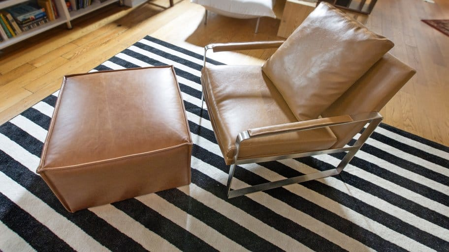 leather chair on black, white striped area rug