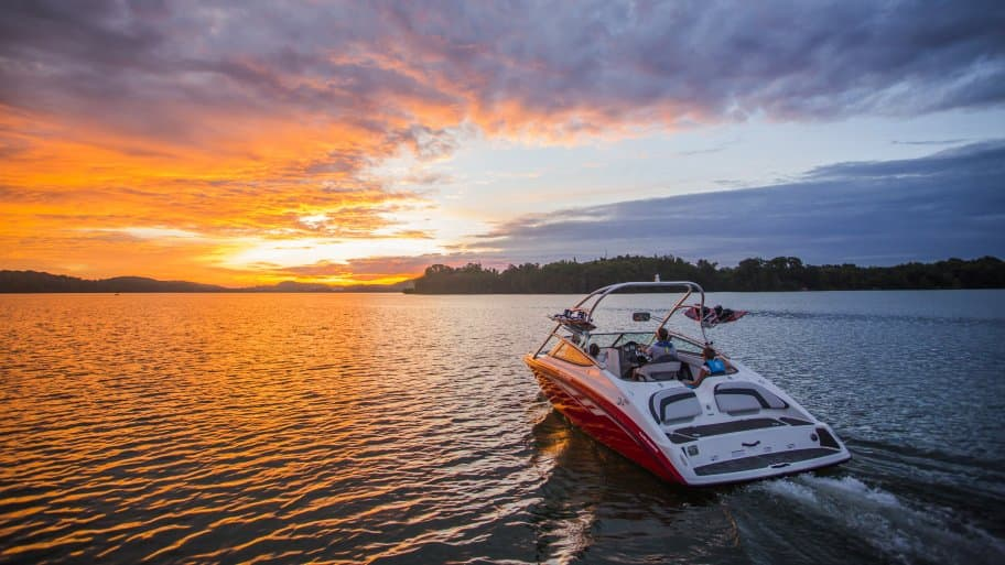red speed boat on lake at sunset