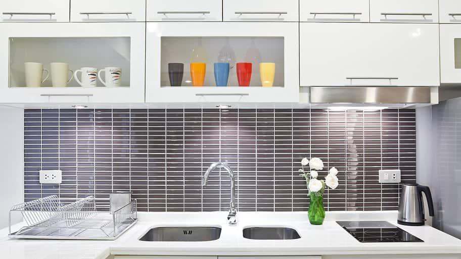 under cabinet lighting in white kitchen with gray subway tile backsplash