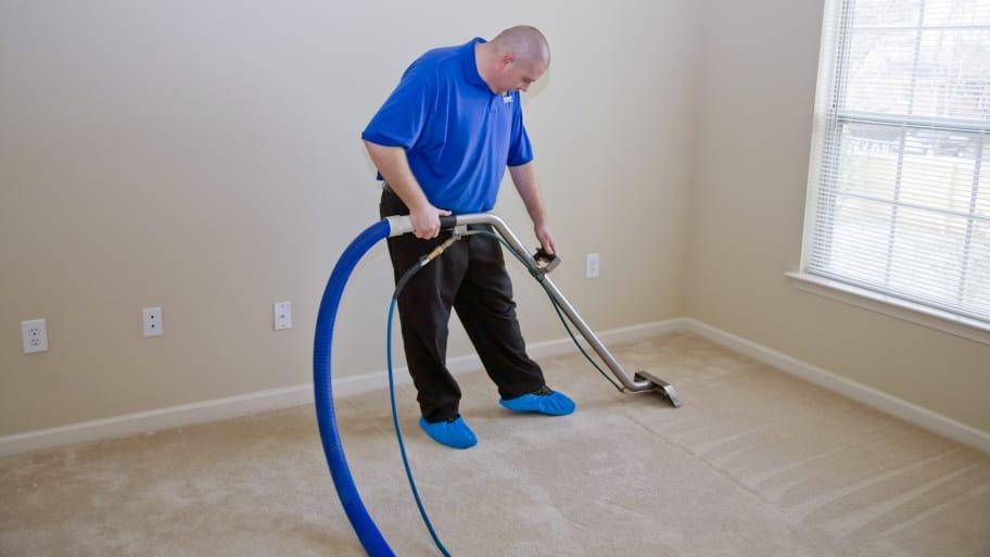 a professional carpet cleaner cleans a carpet
