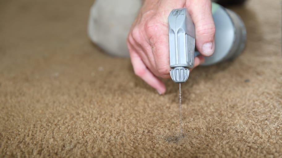 man spraying carpet dye onto carpet