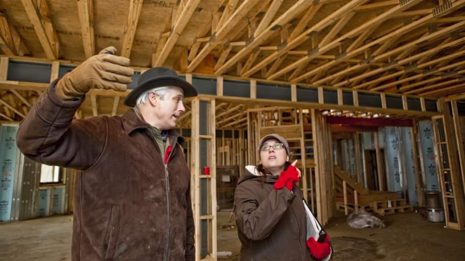 contractor and homeowner inspect construction site