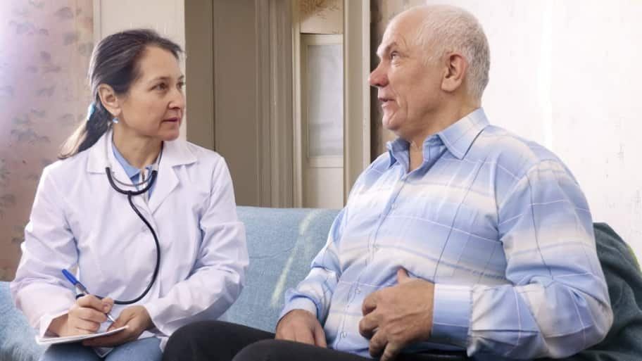 a female doctor takes notes as a elderly male patient explains stomach symptoms.