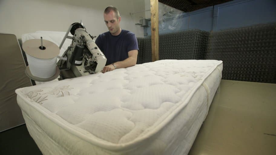 technician sewing mattress together