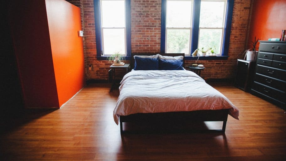 bed in front of exposed brick wall and windows